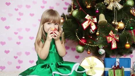 Niña-Comiendo-Una-Manzana-Cerca-De-Un-árbol-De-Navidad-Ella-Se-Sienta-En-El-Piso