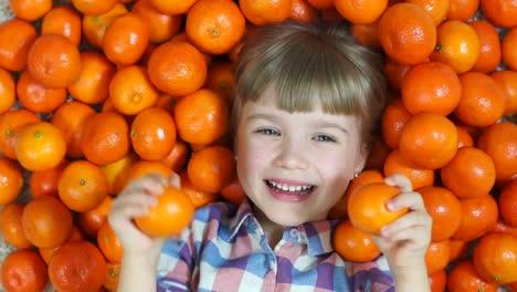 Girl-Orange-Happy-Child-Lying-In-Oranges-Girl-Looking-At-Camera