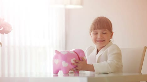 Girl-sitting-at-table-and-holding-piggy-bank