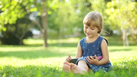 Happy-Niño-With-A-Tablet-PC-Sitting-On-The-Grass-Thumbs-Up-Ok