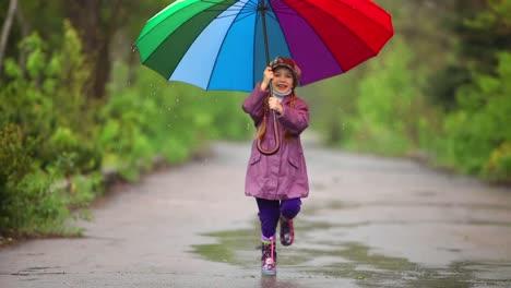 Glückliches-Kleines-Mädchen-Mit-Regenschirm-Das-Den-Weg-Im-Park-Entlang-Läuft