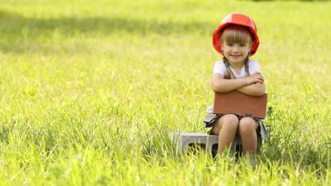 Little-Girl-In-The-Construcción-Helmet-Sits-On-Cinder-Block