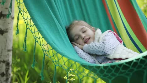 Little-Girl-Lying-In-A-Hammock-And-Smiling-At-Camera