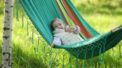 Little-Girl-Lying-In-A-Hammock-And-Swings-And-Smiling-And-Looking-At-Camera