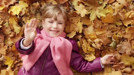 Little-girl-lying-in-yellow-Autumn-leaves