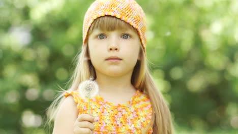 Kleines-Mädchen-Drehte-Sich-Um-Und-Bläst-Einen-Löwenzahn-In-Die-Kamera