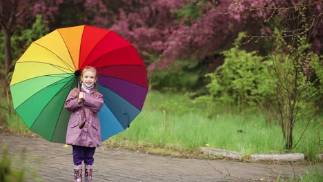 Little-Girl-With-An-Umbrella-In-The-Rain-In-The-Park-Child-Waving-Hand