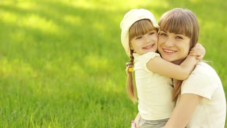 Madre-E-Hija-Abrazándose-Y-Mirando-A-Cámara