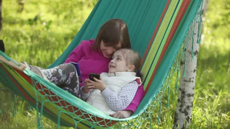 Mother-And-Daughter-Lying-In-A-Hammock-Outdoors-They-Held-Mobile-Phones