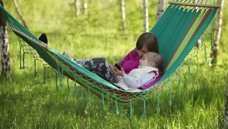 Mutter-Und-Tochter-Liegen-Draußen-In-Einer-Hängematte-Und-Halten-Mobiltelefone