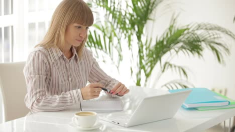 Pretty-Young-Businesswoman-Sitting-At-Table-Working-On-Laptop-And-Writing