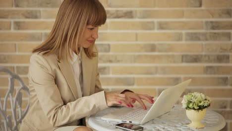 Pretty-Young-Woman-Sitting-At-Cafe-And-Using-Laptop