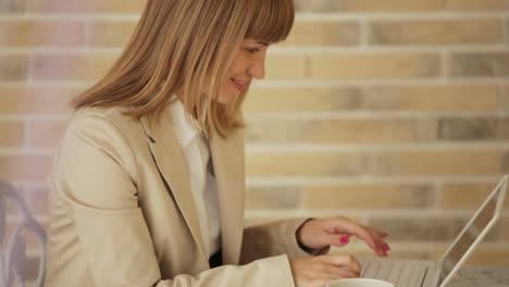 Bastante-Joven-Mujer-Sentada-En-El-Café-Con-Laptop-Y-Taza-De-Café