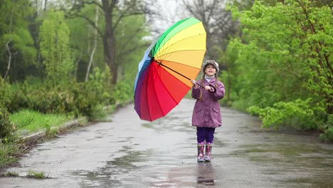 Rain-Happy-Little-Girl-With-Umbrella-In-Hands-Spinning-On-Rain