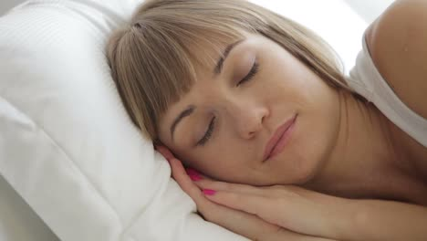 Sleepy-Young-Woman-In-Bed-Opening-Her-Eyes-And-Smiling