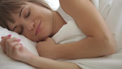 Sleepy-Young-Woman-Lying-In-Bed-Waking-Up-And-Smiling