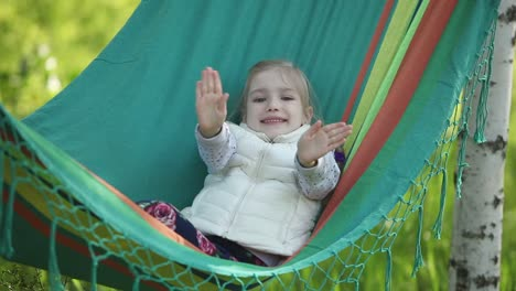 Smiling-Little-Girl-In-A-Hammock-Outdoor-And-Looking-To-The-Camera
