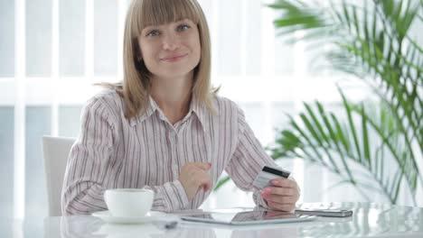 Sonriente-Mujer-Joven-Sentada-En-La-Mesa-Con-Touchpad-Y-Con-Tarjeta-De-Crédito