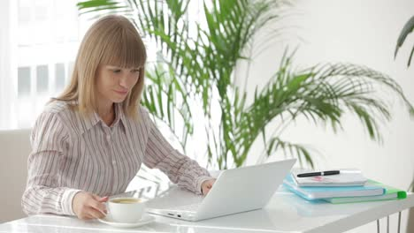 Young-Businesswoman-Sitting-At-Table-Using-Laptop-Holding-Cup-Of-Coffee