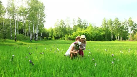 Young-Mother-And-Niño-With-Flowers-In-The-Field-Look-At-Camera-Dolly
