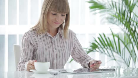 Young-Woman-Holding-Credit-Card-Using-Touchpad-And-Smiling