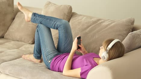 Young-Woman-Lying-On-Couch-With-Phone-And-Listening-To-Music