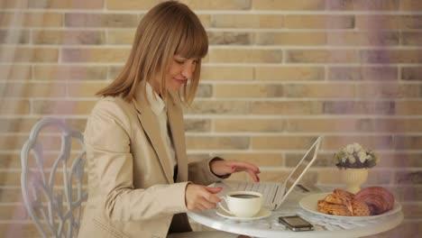 Mujer-Joven-Sentada-En-El-Café-Usando-Laptop-Y-Tomando-Café