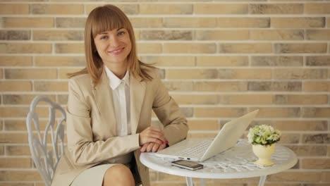 Mujer-Joven-Sentada-En-El-Café-Usando-Laptop-Y-Sonriendo