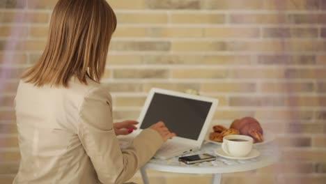 Mujer-Joven-Sentada-En-El-Café-Con-Laptop-Y-Sonriendo-A-La-Cámara