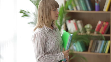 Young-Woman-Standing-Holding-Paper-Folders-And-Smiling-At-Camera