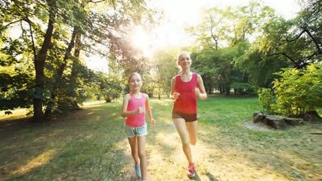 Athletenmutter-Und--tochter-Die-Im-Park-Im-Sonnenlicht-Vor-Der-Kamera-Laufen