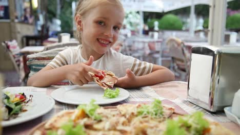 Baby-Girl-Eating-Pizza-In-The-Restaurant-And-Looking-At-Camera