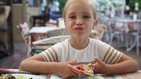 Hermosa-Niña-Comiendo-Pizza-En-La-Cafetería-Y-Mirando-A-La-Cámara-Infantil-Sentado