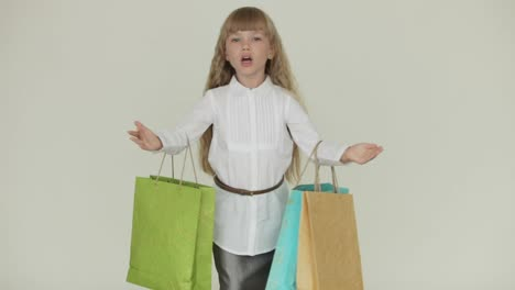 Beautiful-Little-Girl-Holding-Multicolored-Paper-Bags-And-Blowing-Kiss