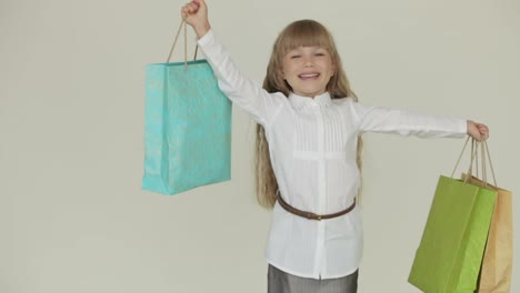 Beautiful-Little-Girl-Posing-With-Multicolored-Paper-Bags-Laughing-And-Smiling