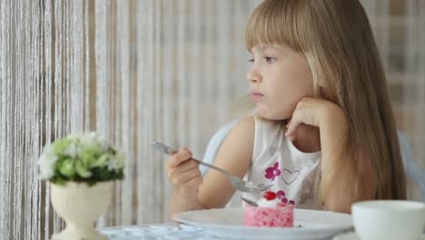 Beautiful-Little-Girl-Sitting-At-Cafe-And-Eating-Cake