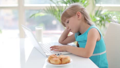 Beautiful-Little-Girl-Sitting-At-Table-Leaning-On-Her-Hand-And-Using-Laptop