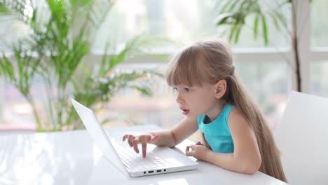 Hermosa-Niña-Sentada-En-La-Mesa-Usando-Laptop-Y-Sonriendo-A-La-Cámara