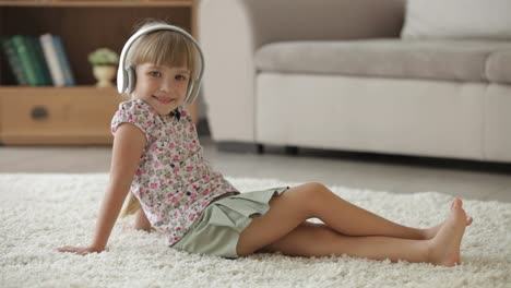 Beautiful-Little-Girl-Sitting-On-Floor-In-Living-Room-Listening-To-Music