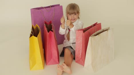 Beautiful-Little-Girl-Sitting-On-Floor-Looking-Into-Shopping-Bags-Showing