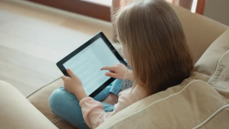 Blond-Girl-Sitting-On-A-Sofa-And-Using-Tablet-PC-Child-Is-Online