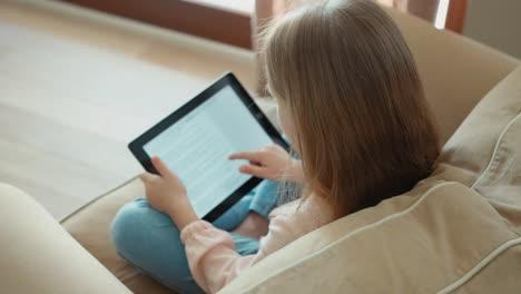 Chica-Rubia-Sentada-En-Un-Sofá-Y-Usando-Tablet-Pc-Niño-Está-En-Línea