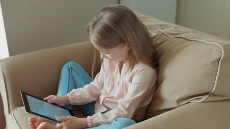 Niña-Rubia-Está-En-Línea-Con-Tablet-Pc-Y-Sentada-En-El-Sofá