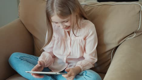 Blond-Little-Girl-Sitting-On-The-Couch-And-Is-Online-With-Tablet-PC