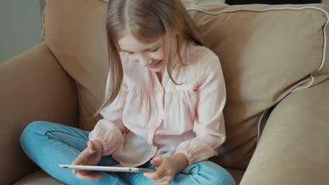 Niña-Rubia-Sentada-En-El-Sofá-Y-Está-En-Línea-Con-Tablet-Pc
