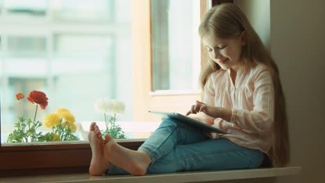 Niña-Rubia-Con-Tablet-Pc-Sentado-En-El-Alféizar-De-La-Ventana-Niño-Sonriendo