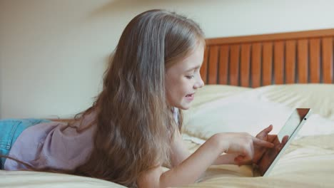 Blonde-Girl-Using-Tablet-PC-On-The-Bed-Child-6-8-Years-Lying-On-The-Bed