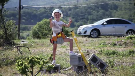 Builder-In-The-Construction-Helmet-And-With-Sunglasses-Child-Is-Holding-Tools