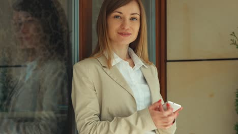 Business-Woman-Using-The-Cellphone-Looking-And-Smiling-At-Camera