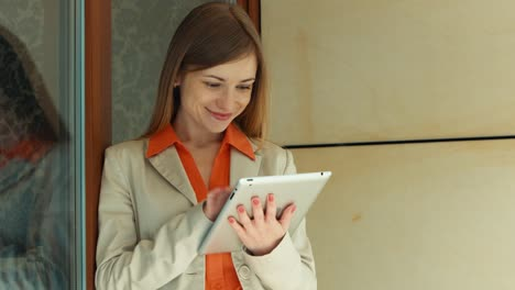 Businesswoman-Using-Touchpad-And-Looking-At-Camera-Thumbs-Up-Ok